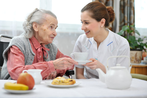caregiver assisting elderly patient in walking